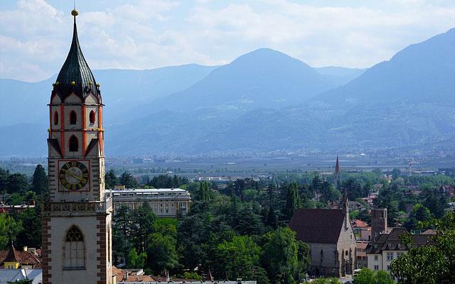 Kirche vor Stadtkulisse und Berglandschaft